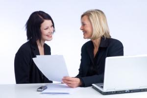 zwei Kolleginnen besprechen die Arbeit, das Notebook steht am Schreibtisch